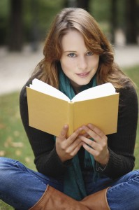 Beautiful young brunette with blue eyes reading a book,sitting in a park