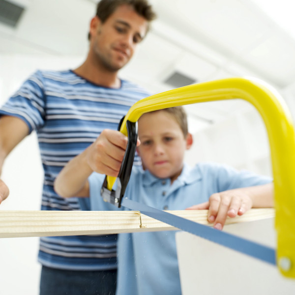 Boy Sawing Piece of Wood in Half with His Father --- Image by © Royalty-Free/Corbis