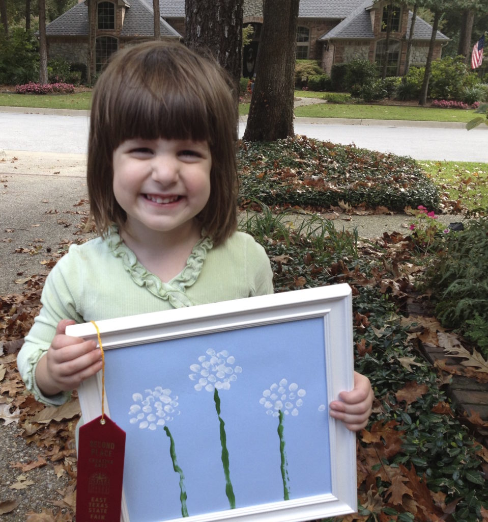 Abby shows off her prize-winning fingerpainting for the State Fair Creative Arts Contest .