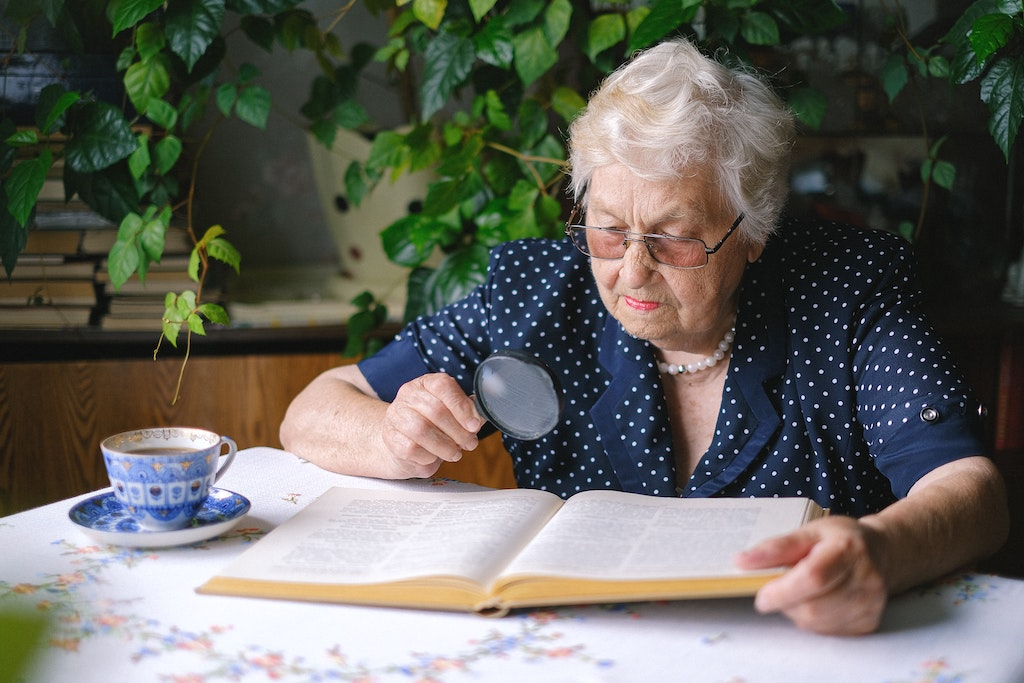 Woman Reading with Magnifying Glass